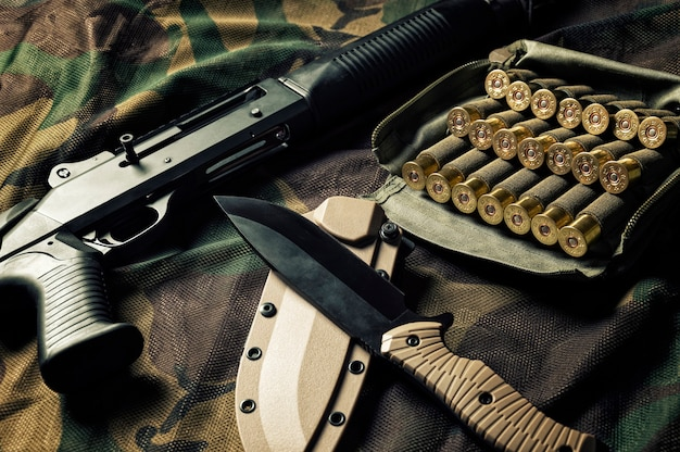 Set of weapons of a fighter of a special unit. shotgun, cartridges, knife.