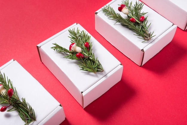 Set of white cardboard boxes decorated with christmas tree ornament on red background