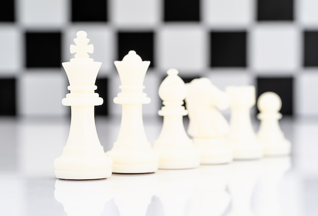 Set of white chess pieces on white background