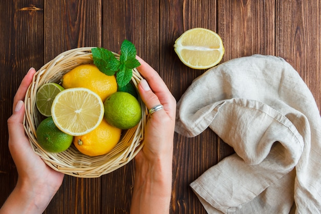 Set of white cloth hand holding lemon basket and lemons in a basket on a wooden surface. top view.