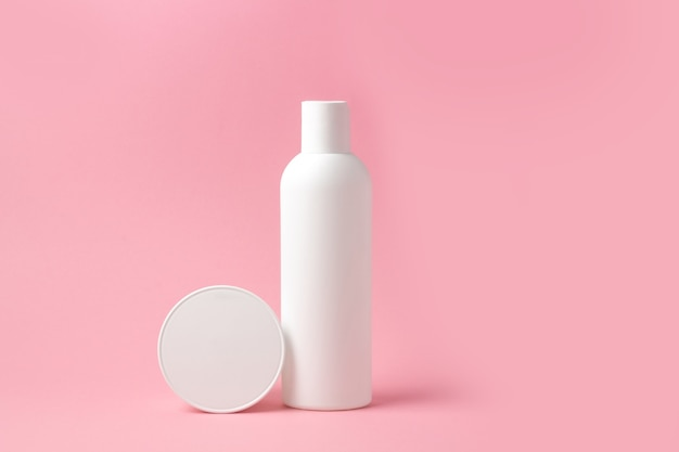 Set of white cosmetic bottles and jars on pink background with place to add text