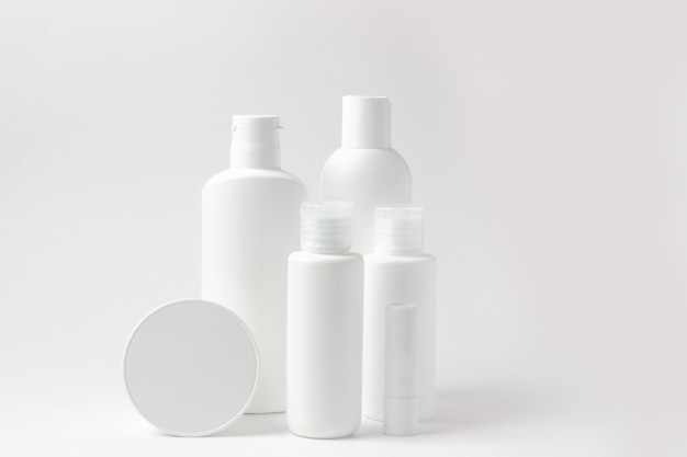 Set of white cosmetic bottles and jars on white background with place to add text