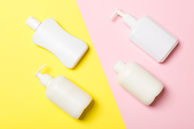 Set of white cosmetic containers isolated on yellow background, top view with copy space. group of plastic bodycare bottle containers with empty space for you design.