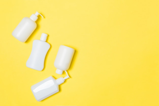 Set of white cosmetic containers on yellow background with copyspace