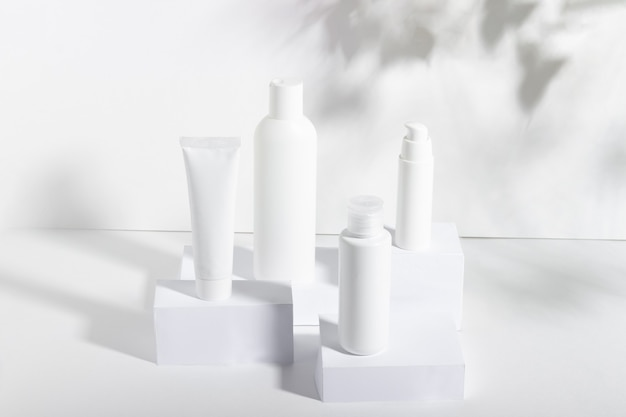 A set of white cosmetic jars on square stands with shadows. toothpaste, face and body cream, hair shampoo. professional cosmetics for skin care. organic cosmetics.