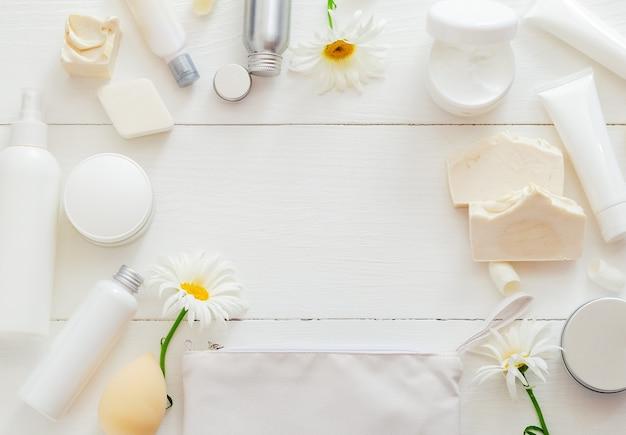 花のある木製のテーブルに白い化粧品フレームを設定します。ビューティースキンケアヘアトリートメントコスメティックセラムオイルモイスチャライザースキンクリームボディバターソープローションシャンプー。フラットレイコピースペース。