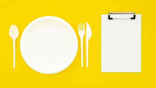 Set of white dish and clipboard on yellow background