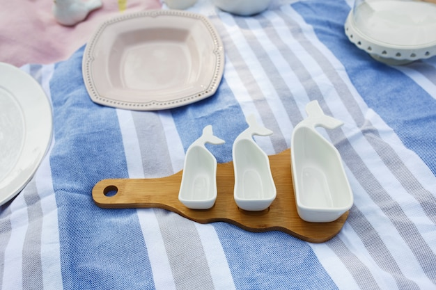 Set of white empty sauceboats on a wooden tray serves a picnic