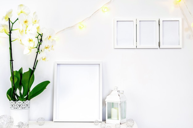 Set of white home decorations with flowers, photo frames and candles