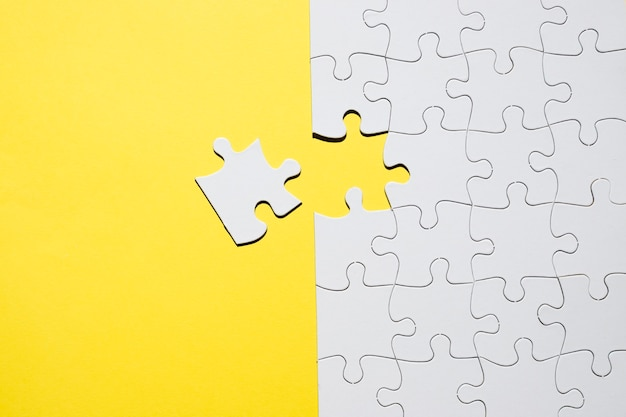Set of white jigsaw puzzle pieces over yellow backdrop