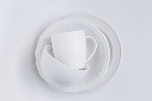 Set of white utensils in a stack of three different plates and a cup