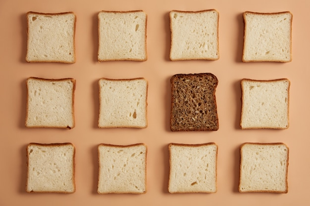 Set of white and wholegrain bread slices on light beige background. rectangular pieces of bread made of organic flour, one is dark prepared for toasting. top view from above, flat lay. pastry food.