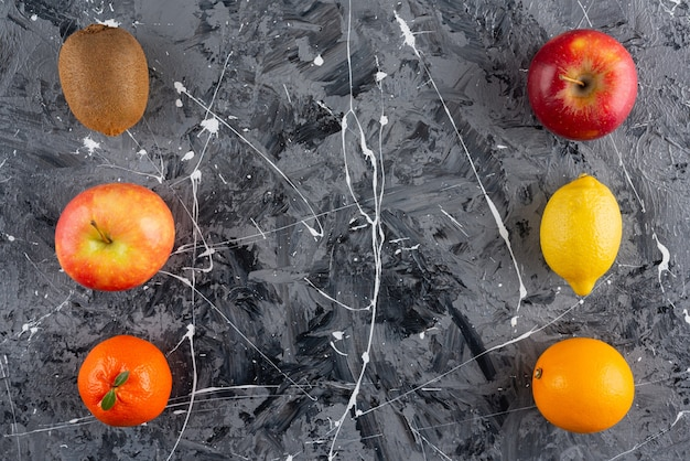 Set of whole delicious organic fruits on marble surface.