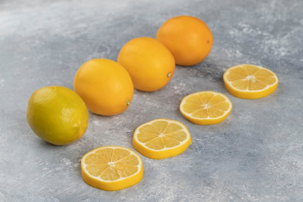 Set of whole sour lemons with slices on a marble background.