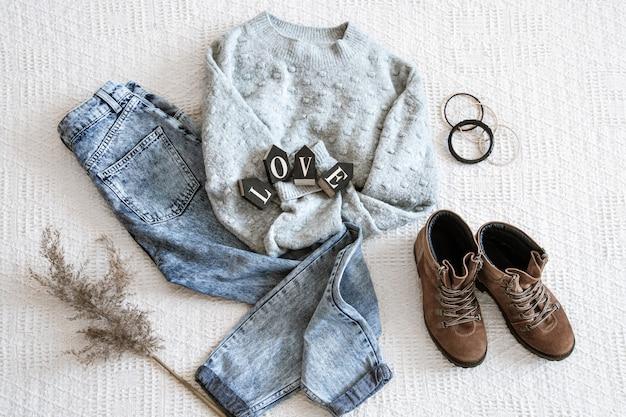 Комплект с модной женской одеждой джинсов и свитер.