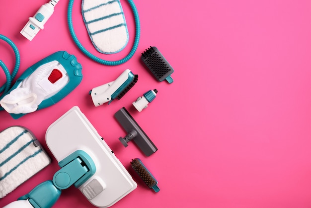 Set with modern professional steam cleaners on pink background.