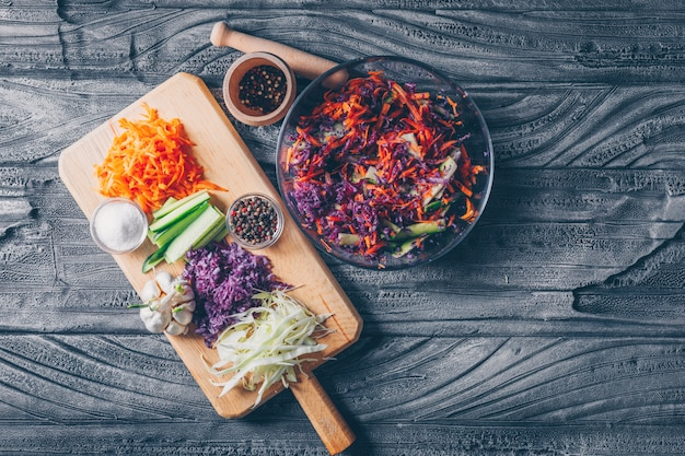 Set of with other chopped vegetables on a cutting board and vegetable salad in a bowl on a dark wooden background. top view.