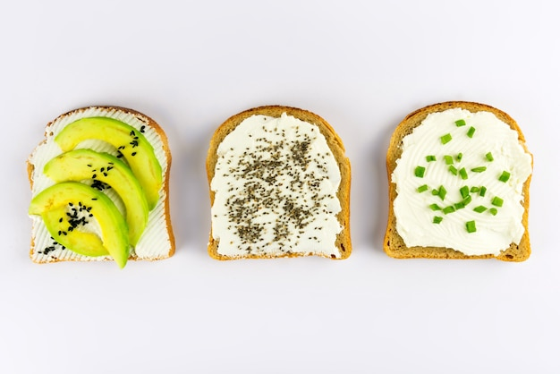 Set with toast bread and different toppings with superfoods, chia seeds, sesame seeds on white surface, top view