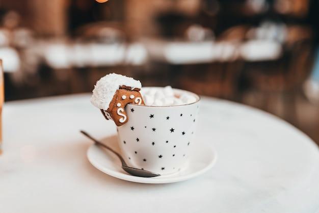 모형을위한 흰색 머그잔으로 설정하십시오. 가장자리에 크리스마스 장식과 쿠키가있는 머그잔