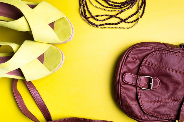 Set of woman's things accessories to summer season. brown bag yellow platform sandals, necklace. flat lay.