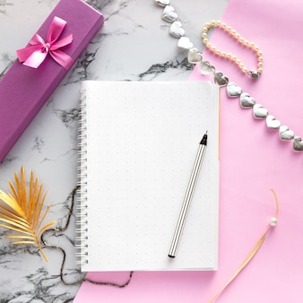 Set of women's accessories desk - notebook with pen, gifts, jewelry, bracelet, golden palm leaf on pink marble background, top view