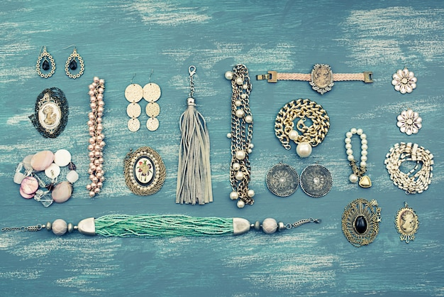Set women's jewelry on wooden background.