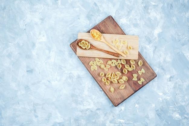 Set di pezzo di legno e pasta cruda in cucchiai di legno su sfondo sgangherata e tagliere. vista dall'alto.