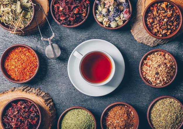 Set di tronchi di legno e una tazza di tè ed erbe di tè in una ciotole su uno sfondo scuro con texture. disteso.
