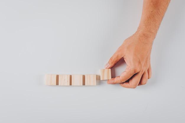 Insieme dei blocchi di legno e dell'uomo che tengono blocco di legno su bianco