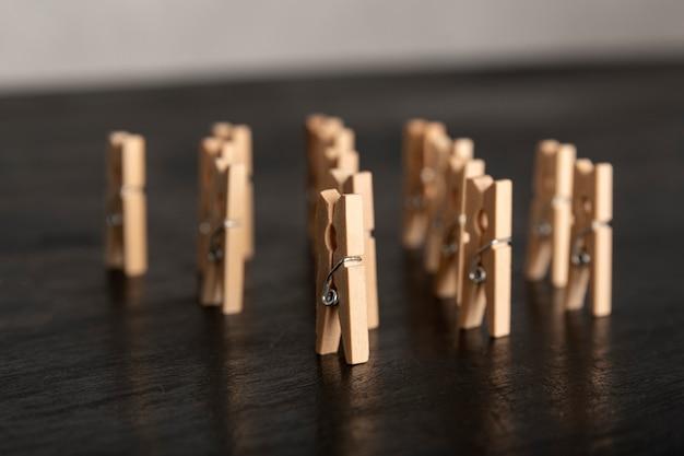 暗い表面に木製の洗濯はさみスタンドをセットします。人々のグループ会議のコンセプト。