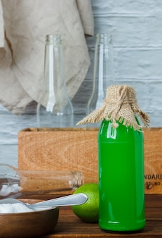 Set of wooden crate and white cloth and lemon juice bottle on a wooden and white surface. side view. space for text