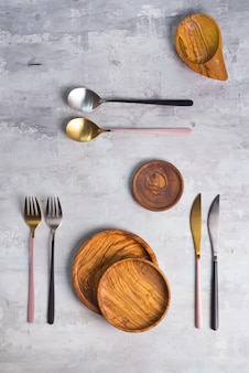 Set of wooden kitchen utensils made from olive wood with stylish pink cutlery