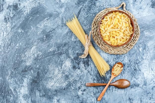 Set di cucchiai di legno e pasta assortita in una ciotola su intonaco grigio e sfondo tovaglietta di vimini. vista dall'alto.
