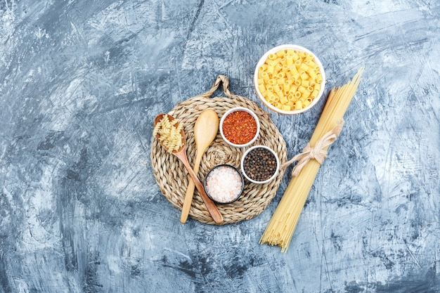 Set of wooden spoons, spices and assorted pasta in a bowl on grey plaster and wicker placemat background. top view.