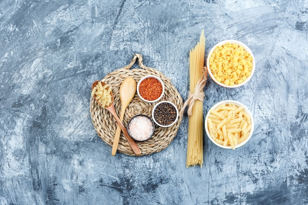 Set of wooden spoons, spices and assorted pasta in bowls on grey plaster