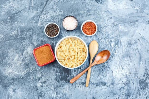 Set of wooden spoons, spices and fusilli pasta in a white bowl on a grey plaster background. top view.