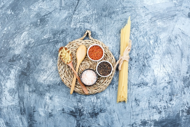 Set of wooden spoons, spices and spaghetti on grey plaster and wicker placemat background. top view.