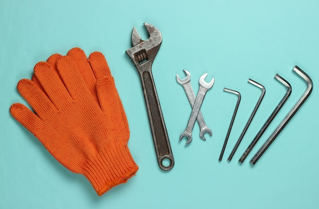 Set of wrench and gloves on blue background. work tool. top view