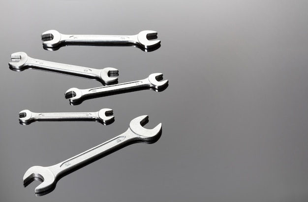 Set of wrenches on a gray background. mirror surface. view on a plane.copy space.mirror surface.