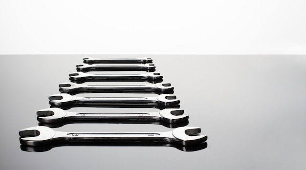 Set of wrenches on a gray background. mirror surface. view on a plane.copy space.