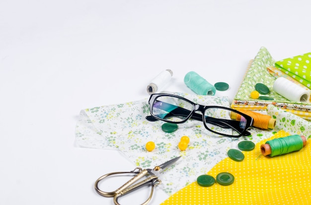 Set of yellow and green fabrics, scissors, buttons, spools of thread and glasses on yellow