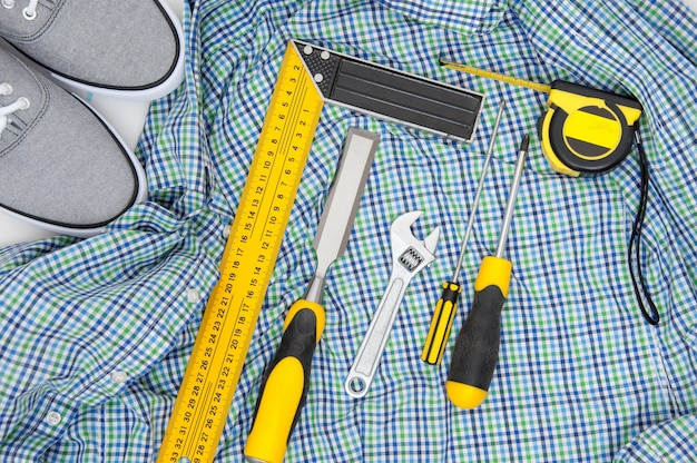 Set  yellow tools on checkered shirt and sneakers top view. men's hobby flat lay .
