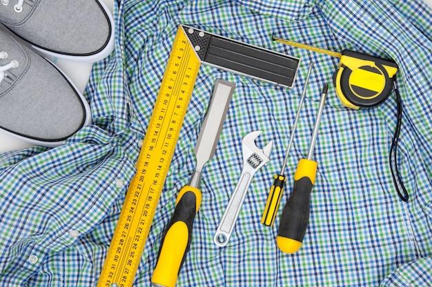市松模様のシャツとスニーカーの上面に黄色のツールを設定します。メンズホビーフラットレイ。