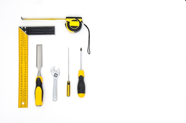 Set  yellow tools on white background top view. carpenter working table. carpentry and woodwork industry flat lay.