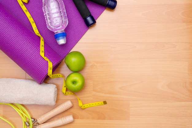 Set of yoga practice with purple mat and dumbbell and towel and bottle of water