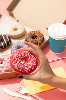 Set of yummy colorful donuts in paper box on pink online delivery take away food