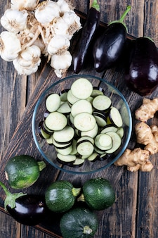 Set of zucchini, garlic, ginger and sliced eggplants in a bowl on a wooden table. top view.