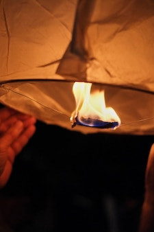 Sets fire to a heavenly paper lantern before launching into the dark evening sky