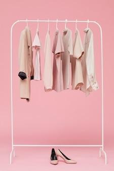 Комплекты одежды, висящие на вешалке с обувью на полу, изолированы на розовом фоне
