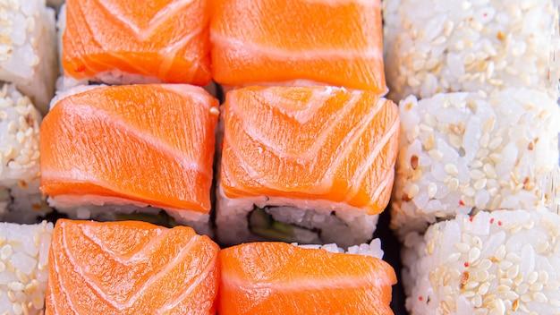 鮭、ご飯、ごまをのせた巻き寿司のセットです。上面図。大きい。ソフトフォーカス。日本の寿司、おやつ、おいしい料理のコンセプト。